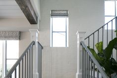 The white exposed brick on this staircase compliments the plaster walls and metal railings very nicely. Brick, Home, Home Construction, Exposed Brick, Stair Railing, Custom Homes, Interior, Custom Home Builders, Luxury Estate
