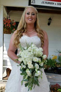 Hydrangea, white roses, white lisianthus, wax flower and seeded eucalyptus wedding bouquet.