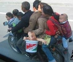 First off, why are there 7 people on the motorcycle and why is the baby in a bucket?