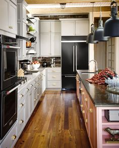 """The KitchenAid double wall convection oven, French-door refrigerator, and dishwasher (at right) in the new black stainless steel finish all offer """"the latest smart technology,"""" says designer Ken Fulk."""