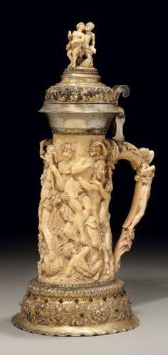 Important vidrecome en ivoire et monture, base et col en métal doré à décor d'entrelacs et fruits en repoussé ; le couvercle est surmonté d'une femme et d'un satyre ; le corps central est décoré d'une femme et d'un satyre. La prise est constituée d'une femme et de feuilles d'acanthe. Fin du XIXème siècle. H.: 46cm