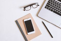 Flat lay photo of office desk with laptop, smartphone, eyeglasses and notebook with copy space background