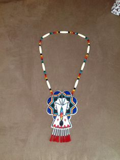 """Necklace 11/0 cuts. Teepee is bordered by multicolor rhinestones. 6"""" long, 5"""" wide. Drops are tin cones with red horsehair. Necklace 8 mm glass beads with hairpipe. November 2014 Scott Sutton."""
