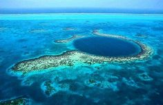 The Great Blue Hole is a large underwater sinkhole off of the coast of Belize. It lies near the center of Lighthouse Reef, a small atoll 45 miles from the mainland and Belize City. The hole is circular in shape, over 1,000 feet across and 400 feet deep. It was formed as a limestone cave system during the last ice age when sea levels were much lower. As the ocean began to rise again the caves flooded, and the roof collapsed.