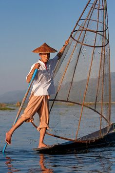 Myanmar, Burma.  Fisherman Looking for a Place to Set his Net, while rowing with one leg, in the style common to Inle Lake, Shan State. Cecil Images