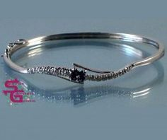 This gorgeous curve bangle bracelet is crafted in sterling silver with prong set sparkling cubic zirconia and four faceted iolite gemstones amid. Rhodium plated. 2.25 inch wide diameter. Clasp Slide Insert Clasp with a Safety Catch. Stone Size 2 mm.  Metal: Silver Setting on/with 925 sterling silver