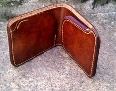 Handmade distressed brown leather wallet, with purple zipper coin bag. Inside, there's room for some cards and two bill compartments, one of them made of cork.