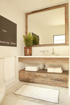 Lovely powder room features reclaimed wood mirror over floating reclaimed wood vanity paired with white top and wall-mounted faucet stacke dover reclaimed wood cabinet atop white penny tiled floor.