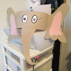 "Horton Hears a Who Hat – Cut 2 4.5""x18"" grey strips. Draw Horton type eyes on white paper & cut out, glue to the center of 1 of the grey strips. Cut 2 elephant ear shapes out of grey paper, at the inner part of the ear draw a flap that is connected to the ear before you cut out it will help you attach it. Cut 2 pink inner ears & glue to center of ears. Cut elephant trunk out – at the end of the trunk cut it so it curls around & has a hole in the center–flower goes here. Continued on 2nd post"