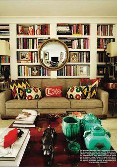 Colorful pillows (I spy Martyn Lawrence-Bullard!) + bullseye mirror behind sofa, hanging on bookshelves