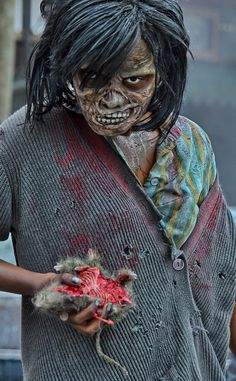 """HHN 22, Universal Studios Florida    One of the Walkers from Halloween Horror Nights 22′s """"The Walking Dead"""" scarezone gets a little hungry and opts for a lighter lunch option.    Photo byMark Walter."""