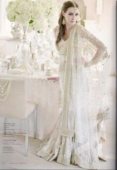 This pure white bridal lehenga choli is the perfect fusion wedding dress. An unusual criss-cross cropped top sets off a full skirt, and all three pieces are heavily embroidered with beads, pearls, and gold thread. Pakistani Bridal, Bridal Lehenga, Pakistani Dresses, Lehenga Choli, Net Lehenga, Desi Wedding, Wedding Attire, Wedding Sari, Wedding Blog