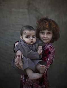 Khalzarin Zirgul, age 6, holds her cousin, Zaman, age three months. | 21 Powerful Portraits Of Afghan Refugee Children
