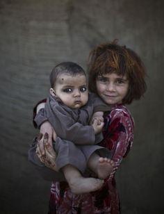 Khalzarin Zirgul, de 6anos, segura seu primo, Zaman, de três meses.  Fotografia: AP Photo/Muhammed Muheisen.