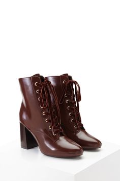 A pair of faux leather ankle boots featuring a lace-up front with grommets, velvet laces, chunky block heel, and a slightly pointed toe.