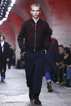 The Belgian designer reinterprets key menswear styles, simplifying and stylizing a more voluminous silhouette. Mixing tartans, floral embroidery, photo prints and the logos of the fabric companies ...