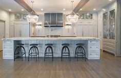 Glamorous gray kitchen boasts two clear beaded chandeliers hung from a white ceiling accented with rustic wood beams over a gray island seating five backless black industrial bar stools between gray drawers donning polished nickel cup pulls and positioned beneath a gray and gold marble countertop.