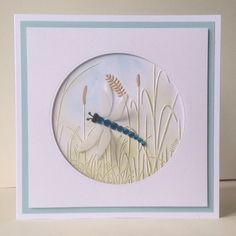 Darice Grass embossing folder coloured with chalk inks and a brown ProMarker for the background with a dragonfly with 2 sets of vellum wings and a jewelled body.