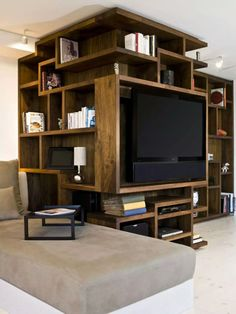 8 TV Wall Design Ideas For Your Living Room // This custom artistic shelving unit that wraps around the corner has a spot that's just the right size for the TV and sound bar to be mounted in.