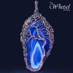 This one of a kind handmade tree of life necklace pendant jewelry was wrapped with pure copper wire and then oxidized to give it a beautiful antiqued look. Many feet of copper wire was artistically wrapped and weaved into this artisan jewelry pendant. The center gemstone is a blue agate slice....
