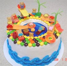 Swimming pool filled with piping gel water. Teddy grahams people. Starburst, licorice,gummi savers, peach ring, Skittles & sour apple sticks for tile decking,chairs, blanket, towel, beach ball, raft, life rings & palm trees.