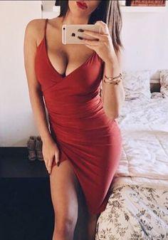 Brunette model poses in red plunge ruched tulip-skirt dress