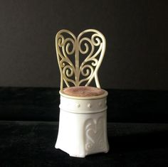On offer is an Avon crème sachet container, in the form of a decorative chair, for their Moonwind fragrance.  The chair base is made of milk glass and