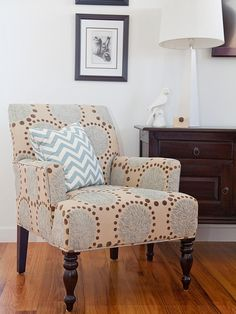 A pretty patterned chair with a gray and white chevron pillow is a stylish and comfortable place to rest in this traditional white living room.