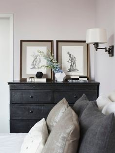 Black chest of drawers and beautiful rich tones. Bedroom art