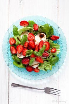 Lekka letnia sałatka z truskawkami, mozzarellą i bazylią, na sałacie, polana sosem balsamicznym. Pełna smaków i kolorów!