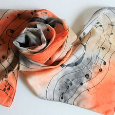 Hand painted silk scarf in orange, gray and tan with musical notes. 100% silk scarf. Hand washable. 14 wide x 70 long (approximately) Gently hand wash silk scarf with a mild detergent. Add fabric softener to rinse. Air dry. Iron with appropriate fabric setting. Thank you for
