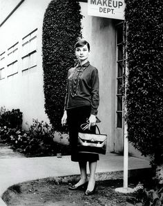 Audrey Hepburn in working girl look - high collar, long double-rounded necklace with a brief case.