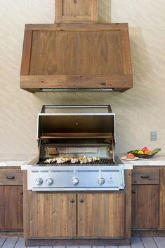 Rustic, worn wood cabinetry and white tile countertops inform this outdoor kitchen space. Stainless steel grill stands below a wood wrapped hood vent.