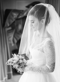 A timeless bride wearing a #MoniqueLhuillier gown and blusher veil and holding a lily of the valley bouquet. Photo: Braedon Photography