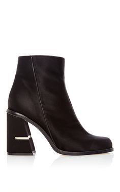 This **Tibi** bootie features a satin body with a rounded toe and a matching block heel with metallic accent.