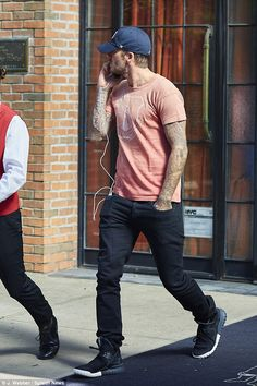 Tat lover: The ex-pro athlete showed off his sculpted stomach in a loose-fitting peach T-shirt, which trimmed his fine form and flaunted his sleeve tattoos