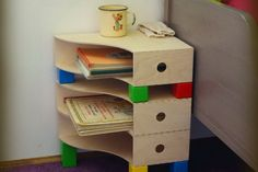 IKEA Hackers - You need three pieces of Knuff magazine files, wooden blocks, hot glue gun. Magazine files and blocks fix together with hot glue gun or another appropriate glue. Ikea Hackers, Bedside Table Ikea, Childrens Bedside Table, Craft Room Tables, Magazine Files, Diy Zimmer, Night Table, Ikea Furniture, Home Organization