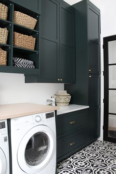 The Laundry/Dog Room: Dark Green Cabinets Layered On Classic Black + White Design - The House of Silver Lining A modern classic black and white laundry room layered with gorgeous dark green cabinets and natural white oak wood accents. White Laundry Rooms, Mudroom Laundry Room, Modern Laundry Rooms, Laundry Room Remodel, Laundry Room Cabinets, Farmhouse Laundry Room, Black Cabinets Bathroom, Laundry Appliances, Laundry Decor