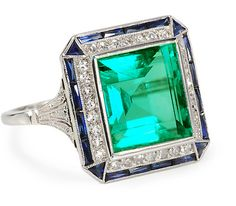 The emerald is estimated at 5.25 carats and is set in platinum. It's framed with thirty old-single-cut diamonds, and four triangular-cut synthetic sapphires sit at the corners, with an additional border of sapphires in between.