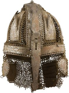 Indian (Deccani) helmet, 16th/17th c, broad central band over the top connected to riveted and solid mail which also connect curved triangular plates with the lower central band, the bottom encircled by five rectangular plates, cheek-plates and an embossed plate over each ear, neck-guard of two rows of rectangular laminated plates, mostly with cusped lower border, two tubular plume-holders, and adjustable nasal with trefoil-shaped terminals, 31 cm. high.