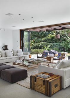 Living Room - accordion glass doors bring the outside in. Tempo House by Gisele Taranto Arquitetura