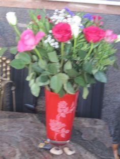 Rose etched on red vase. Pebbles picture of paws.