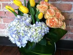 "Situated in a flattened vase, the ""Peachy Blues"" arrangement features light blue hydrangea, ruffled petaled peach roses and yellow tulips. It is accented with various green foliage. Floral design by Kathy Benetatos and Maria Petrides of  Mudd Fleur  in Chicago."