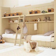 Chambre denfant en planches de bois avec lits tête bêche, étagères et tiroirs camouflés