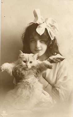Girl with a big bow in her hair, holding up her white cat, 1910s