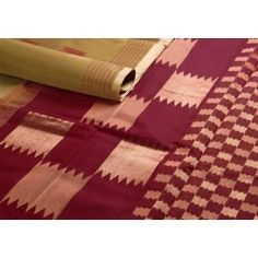 A khaki colour body with simple maroon stripes in the border - what plays up the look is the chess board design in maroon and gold in the pallu!