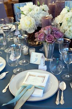 Tables are set with silver-rimmed wine glasses and lush arrangements of roses and peonies.