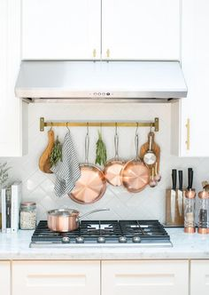 Copper pots hanging over stovetop.