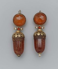 Earrings; 1800's; Italian. Pair of amber earrings, for pierced ears, shaped like acorns, with gilded cap and end, joined to cut amber stud by two seed pearls and orange-coloredjewel.