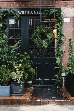 black doors + exposed bricks + plants at 'Wilfie & Nell' entryway | West Village, NYC by Nicole Franzen